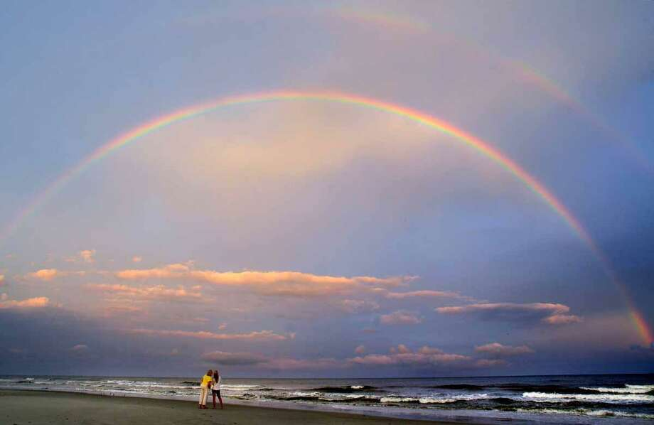 In this photo taken July 30, 2012, beachgoers admire a double rainbow that appeared over Hilton Head Island's South Forest Beach after Monday evening's rains in Hilton Head, S.C. (AP Photo/The Island Packet, Jay Karr) Photo: ASSOCIATED PRESS / AP2012