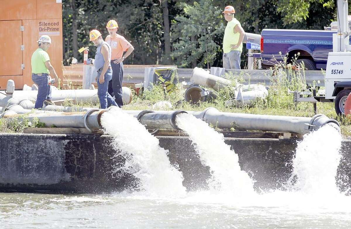 Workers watch water being pumped out near the site of a breach in a wall of the Erie Canal in Albion, N.Y., Wednesday, Aug. 1, 2012. A scenic 25-mile stretch of the Erie Canal in western New York is temporarily off limits to boaters following a partial collapse of the embankment in the Orleans County village of Albion, authorities said Wednesday. (AP Photo/David Duprey)