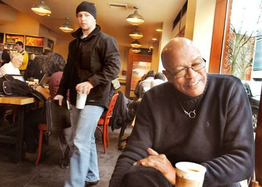 """New Haven_Yale Professor, Elijah Anderson, talks about his book, Cosmopolitan Canopy. He is sitting in Starbuck's, a """"cosmopolitan canopy"""" place where people can safely check each other out.     Melanie Stengel/Register"""