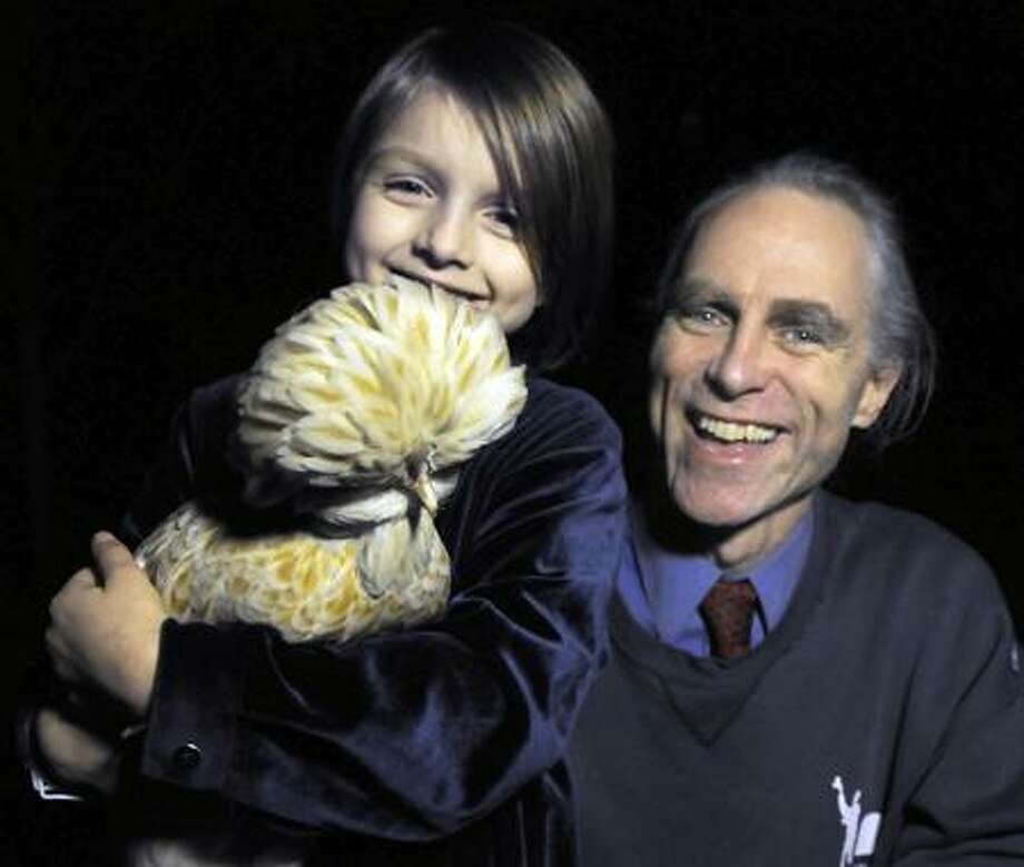 Yale Recycler C.J. May at home in New Haven with his daughter Ella age 6 and their Polish Crested chicken Mazey. Photo by Mara Lavitt/New Haven Register2/1/12