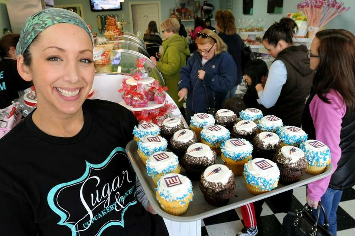 East Haven___ Brenda DePonte, of Sugar Bakery, with some of the Giant's and Patriot's cupcakes featured this Super Bowl weekend. Melanie Stengel/Register
