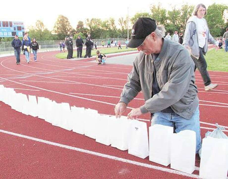 Photo by JOHN HAEGER (Twitter.com/OneidaPhoto) Steve Davies places candles inside bags for the luminary lap during the Relay for Life on Saturday, June 2, 2012.