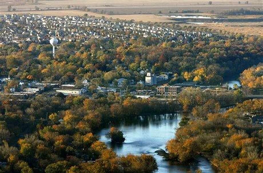 This Oct. 2010 aerial file photo shows the Fox River as it flows into downtown Oswego, Ill., in Kendall County, with subdivisions and farmland to the southeast. The nation's No. 1 fastest-growing county from 2000 to 2010, Kendall was part of an exurban wave in the heady 2000s that more than doubled its population. But Census estimates as of July 2011 highlight a shift in population trends, following an extended housing bust and renewed spike in oil prices. Outlying suburbs are now seeing their growth fizzle to historic lows, halting American city dwellers' decades-long exodus to sprawling homes in distant towns.   Associated Press Photo: AP / The Beacon-News