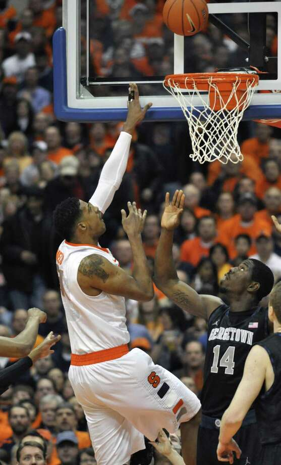 Syracuse's Fab Melo, left, shoots over Georgetown's Henry Sims during the first half of an NCAA college basketball game in Syracuse, N.Y., Wednesday, Feb. 8, 2012. (AP Photo/Kevin Rivoli) Photo: ASSOCIATED PRESS / AP2012