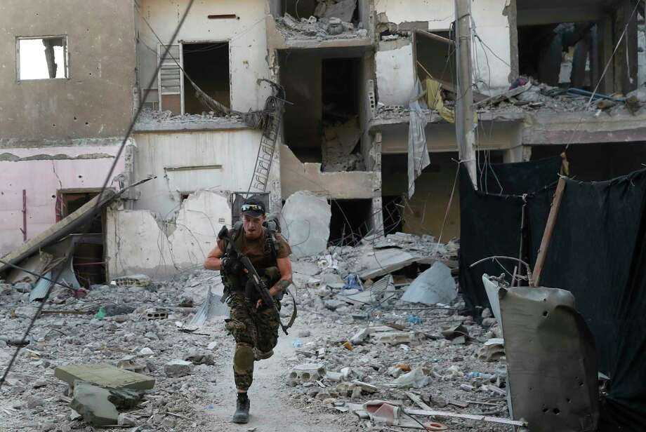 A U.S.-backed Syrian Democratic Forces fighter races away from a damaged building as he crosses a street on the front line Thursday in Raqqa city, northeast Syria. Photo: Hussein Malla, STF / Copyright 2017 The Associated Press. All rights reserved.