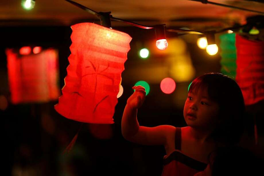 A girl touches a lantern at an outdoor restaurant during the Chinese Mid-Autumn Festival in Hong Kong Sunday, Sept. 30, 2012. Like ancient Chinese poets, Hong Kong people appreciate the beauty of the full moon in the Mid-Autumn Festival.  (AP Photo/Vincent Yu) Photo: ASSOCIATED PRESS / AP2012