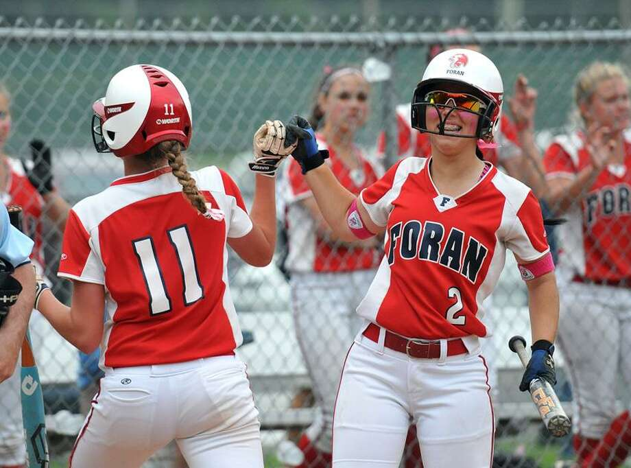 Milford-- Foran's Fallon Bevino (#11) gets the high five from Ashley Mendillo as Bevino crosses the plate during the 6th inning against Wethersfield during the Class L quarterfinal at Foran High School. Peter Casolino/New Haven Register 06/01/2012