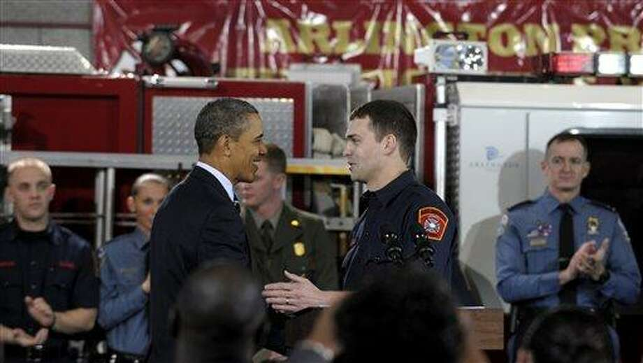 President Barack Obama shakes hands with Arlington County firefighter and U.S. Marine Corps veteran Lt. Jacob Johnson, who served in Iraq, after he was introduced to speak about the economy during an event at Fire Station #5 in Arlington, Va., Friday. Obama has called for putting unemployed veterans to work in conservation projects on public lands. Associated Press Photo: AP / AP