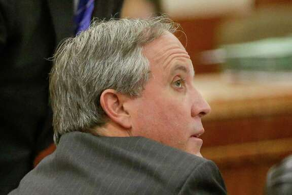 The securities fraud case against Texas Attorney General Ken Paxton, front, shown with Phil Hilder, one of the attorneys representing him, will be heard in a Houston courtroom.