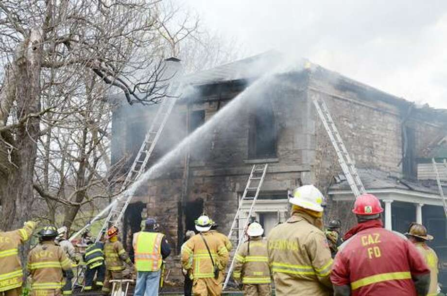 Photo by CAITLIN TRAYNOR Fire crews battle at farmhouse fire on Perryville Road in Chittenango.