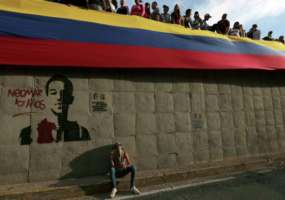 In this Monday, July 24, 2017 photo, a demonstrator sits near a spray-painted stencil of Neomar Lander during a tribute to those killed in the recent wave of protests against Venezuela's President Nicolas Maduro, in Caracas, Venezuela. An AP tally of official reports shows that the death toll in nearly 4 months of civil unrest in Venezuela reached 100 on Thursday, July 27, 2017. Most of the deaths reported by the country's chief prosecutor  since anti-government protests began in April are of young men killed by gunfire. The count also includes looters, police allegedly attacked by protesters and civilians killed in accidents related to roadblocks set up during demonstrations. (AP Photo/Fernando Llano) Photo: Fernando Llano, STF / Copyright 2017 The Associated Press. All rights reserved.