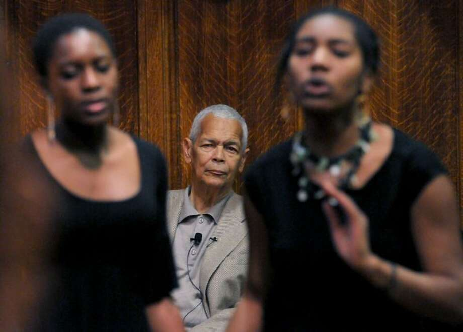 Civil rights icon Julian Bond, center, listens as the Yale acapella group, Shades, including Oluwaseyi Adeyinka, left, and musical director Jasmine Reid, right, sing a medley of Amen/We Shall Overcome before Bond spoke at Strathcona Hall at Yale Thursday. Mara Lavitt/Register