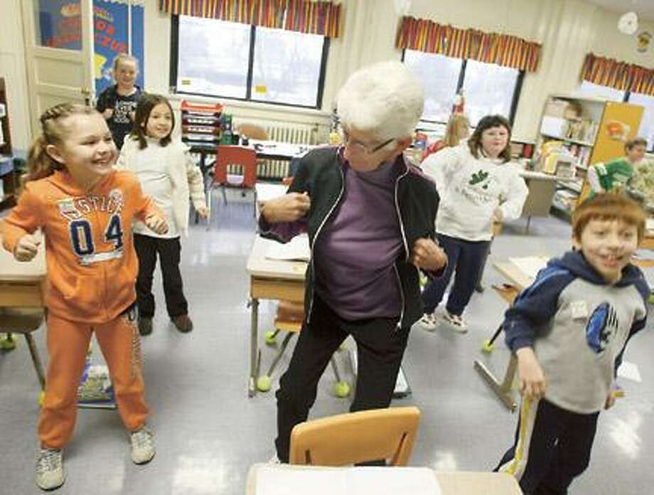 """Dispatch Staff Photo by JOHN HAEGER <a href=""""http://twitter.com/oneidaphoto"""">twitter.com/oneidaphoto</a> St. Patrick's students Karissa Jones and Jared Smith do the chicken dance with Principal Peg Brown  during  """"Get Up & Move"""" during Catholic Schools Week on Thursday."""
