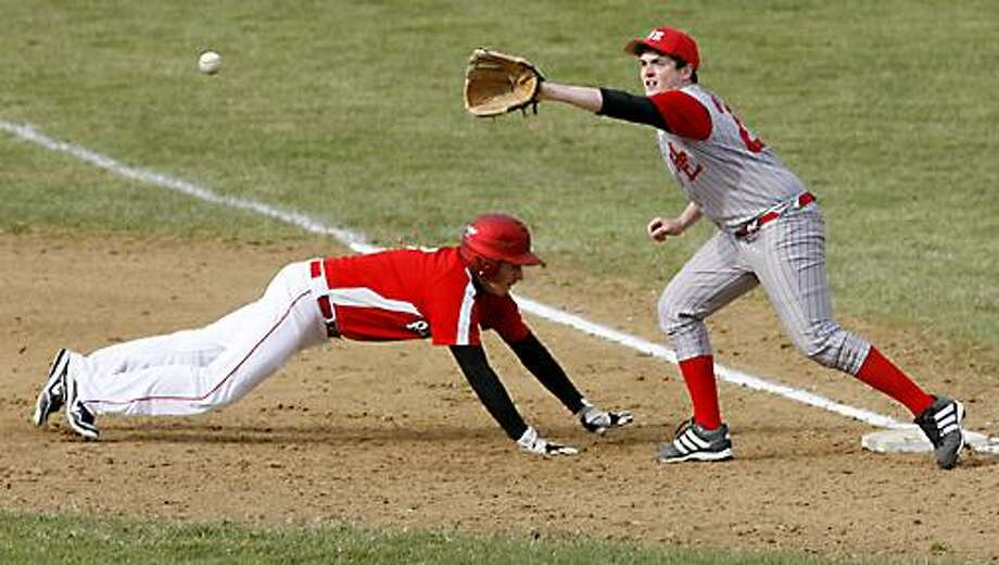 Dispatch Staff Photo by JOHN HAEGER (Twitter.com/OneidaPhoto) RCS' Brian Campbell dives safely back to first as M-E's Chris Hynes waits on the throw in the top of the second inning in Morrisville on Tuesday, April 3, 2012. Rome Catholic won 3-0.