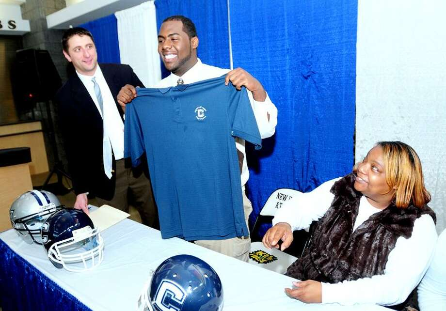 Rennick Bryan (center) holds up a UCONN football shirt after signing a letter of intent to play football at the University of Connecticut at the Floyd Little Athletic Center in New Haven on 2/1/2012.  At left is Hillhouse High School football coach Tom Dyer and at right is Bryan's mother, Donna Perry.Photo by Arnold Gold/New Haven Register   AG0437D