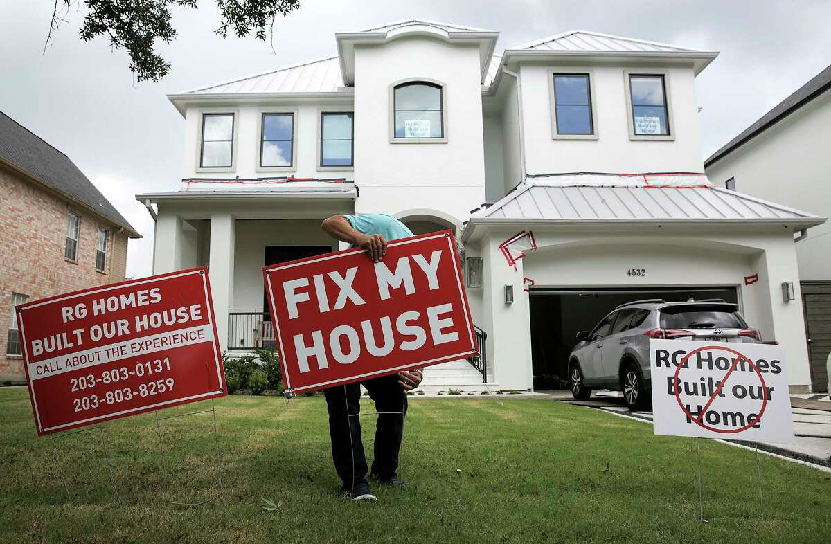 Jim Rowe adjust a signs in front of his home warning neighbors about the builder, RG Homes. Photographed on Wednesday, July 19, 2017, in Bellaire.