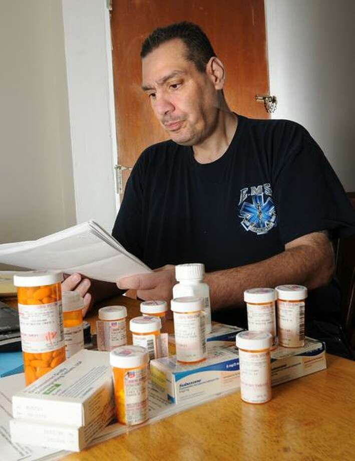 Joe Tomaso of West Haven looks over medical records near some of the medication he takes to stay alive. Tomaso contracted Hepatitis C while working as a paramedic and has now been pre-approved for a liver transplant.   Peter Casolino/Register