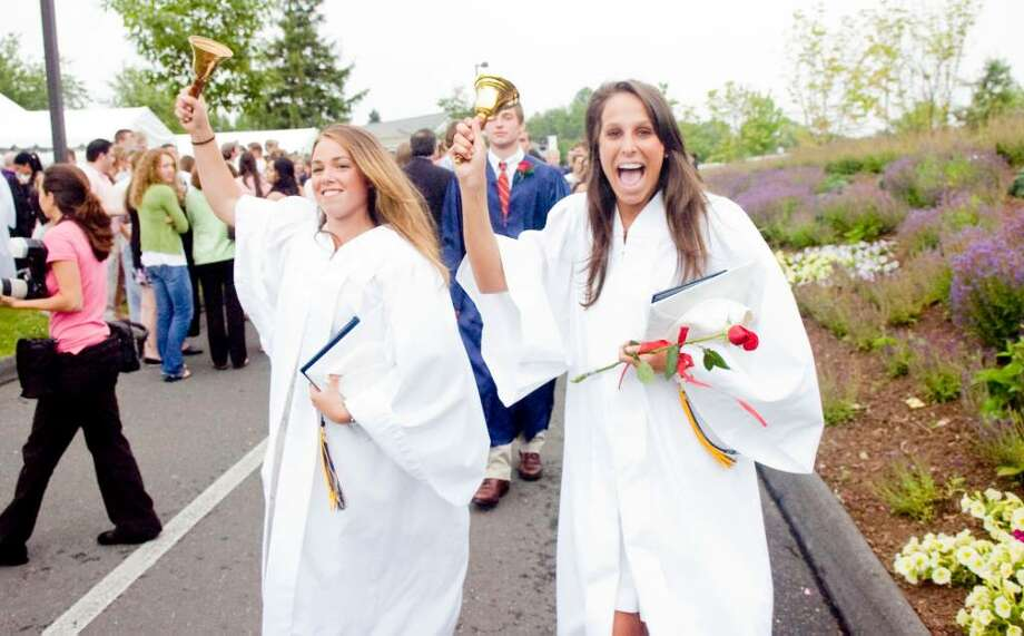 Sabina Armstrong-Loscalzo, left, and Molly Rather ring bells as they exit the King Low Heywood Thomas Commencement celebrating the class of 2010 Sunday June 13, 2010. In a school tradition, the students ring-in the new school year as it begins in the fall and graduates ring as they exit graduation. Photo: Keelin Daly / Stamford Advocate