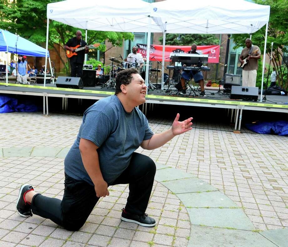Patrick Brandao, of Bridgeport, dances to a Michael Jackson song performed by the Sez Zion Jazz Band during Downtown Thursdays Concert Series at McLevy Green in downtown Bridgeport, Conn., on Thursday July 27, 2017. The Sez Zion Jazz Band, from Bridgeport, formed in 2001. Photo: Christian Abraham / Hearst Connecticut Media / Connecticut Post