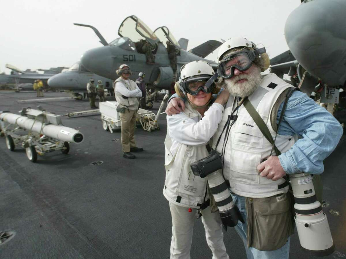 M.L. Lyke and Grant M. Haller stand on the deck of the USS Aircraft Carrier Abraham Lincoln in front of Whidbey Island-based EA-6B Prowlers that just returned from a mission over Iraq. Their escort, stands to the rear, left. Photo taken March 27, 2003.