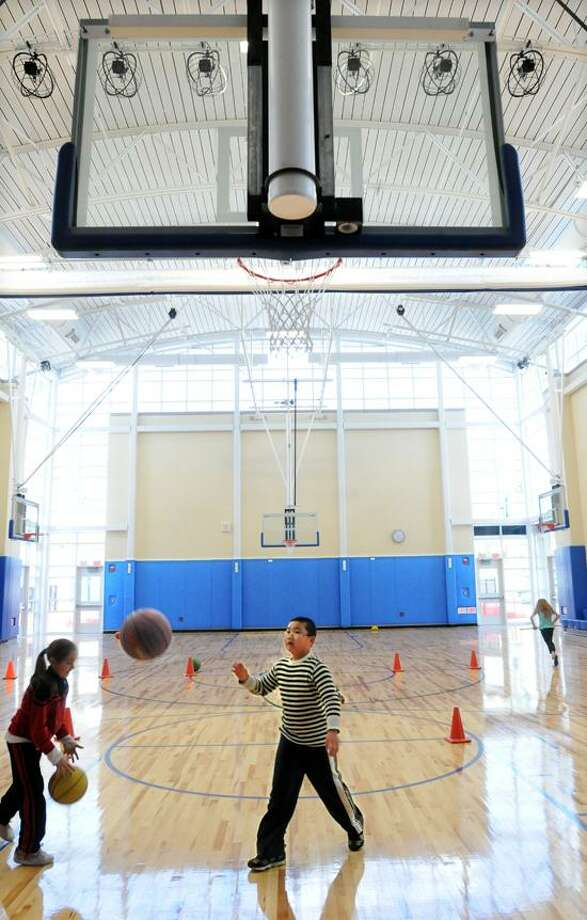 Paul E. Chatfield School in Seymour is being renovated and has some new construction. The gymnasium is part of the new construction and today was the first day children, including third-graders Viktoria Biblekaj, left, and Kenneth Dong, right, could use the new facility.  Mara Lavitt/New Haven Register