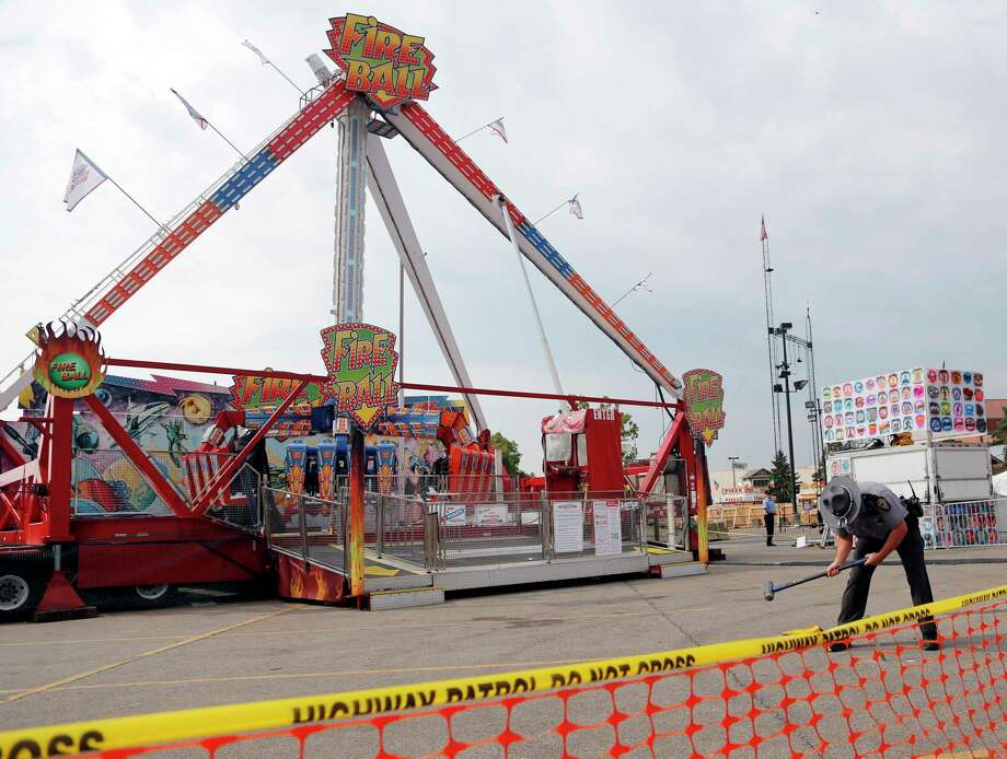 An Ohio State Highway Patrol trooper removes a ground spike from in front of the fire ball ride at the Ohio State Fair Thursday, July 27, 2017, in Columbus, Ohio.  The fair opened Thursday but its amusement rides remained closed one day after Tyler Jarrell, 18, was killed and seven other people were injured when the thrill ride broke apart and flung people into the air. (AP Photo/Jay LaPrete) ORG XMIT: OHJL102 Photo: Jay LaPrete / FR52593 AP