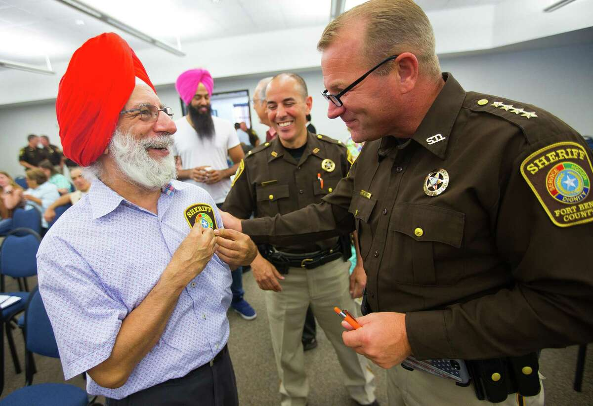 """Fort Bend County Sheriff Troy Nehls says he's not interested in a 287(g) partnership. In this photo, Bhupinder Singh exchanges gifts with Fort Bend County Sheriff Troy Nehls at the """"Diversity and Living Together"""" session held by the sheriff's office Thursday in Richmond."""
