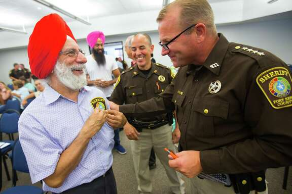 "Bhupinder Singh exchanges gifts with Fort Bend County Sheriff Troy Nehls at the ""Diversity and Living Together"" session held by the sheriff's office Thursday in Richmond."