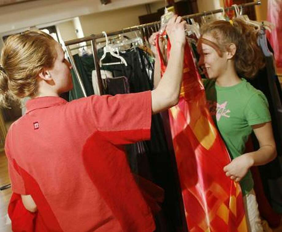 Dispatch Staff Photo by JOHN HAEGER Johanna Graham, left, holds up a prom gown for her sister Teena Graham to look at during last year's First Presbyterian Church prom dress give away on Saturday, April 3, 2010 in Oneida. The Grahams are from Stockbridge.