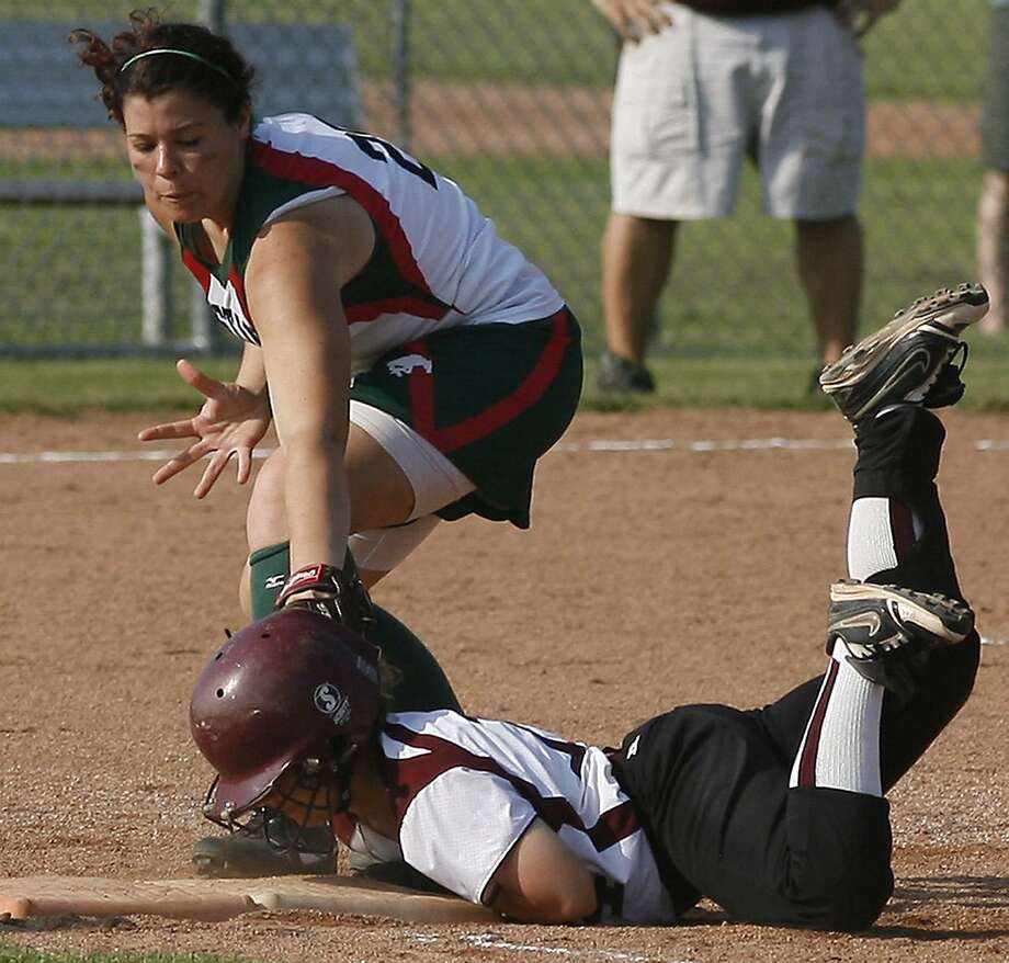 Dispatch Staff Photo by JOHN HAEGER Canastota's Kaliegh Coon (14) dives back to first under the tag of Marcellus Angela Gonnella (25)  in the bottom of the second inning of play in Sec III playoffs in Canastota on Tuesday, May 31, 2011.