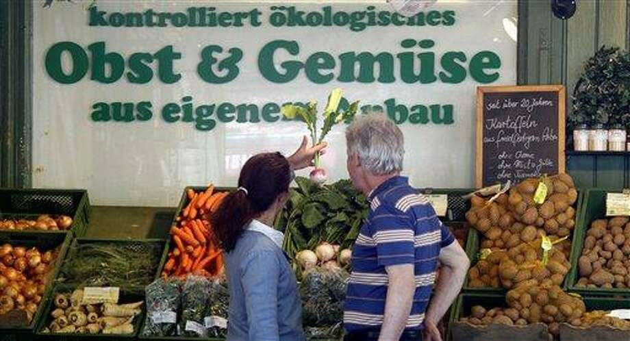 People  look at vegetables at  a fruit and vegetable market in Munich, southern Germany, on Tuesday, May 31, 2011. Germany's national disease control center says the number of people falling ill in connection with a mysterious bacterial outbreak linked to tainted vegetables continues to rise. Robert Koch Institute said Tuesday that more than 1,150 people have been affected by the bacteria and that it has confirmed nine deaths. Sign in background reads: 'Controlled Organic, Fruit and Vegetables, own growing'. (AP Photo/Matthias Schrader) Photo: AP / AP
