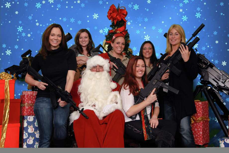 This undated photo provided by the Scottsdale Gun Club shows people posing with Santa Claus and several automatic weapons at the Scottsdale, Ariz. club. Ron Kennedy, general manager of the gun club, says the business got the idea for the photo op last year when a club member happened to come in dressed as Santa and other members wanted their picture taken while they were holding their guns. He says people have used the photos for Christmas cards and Facebook posts. Associated Press Photo: ASSOCIATED PRESS / AP2011