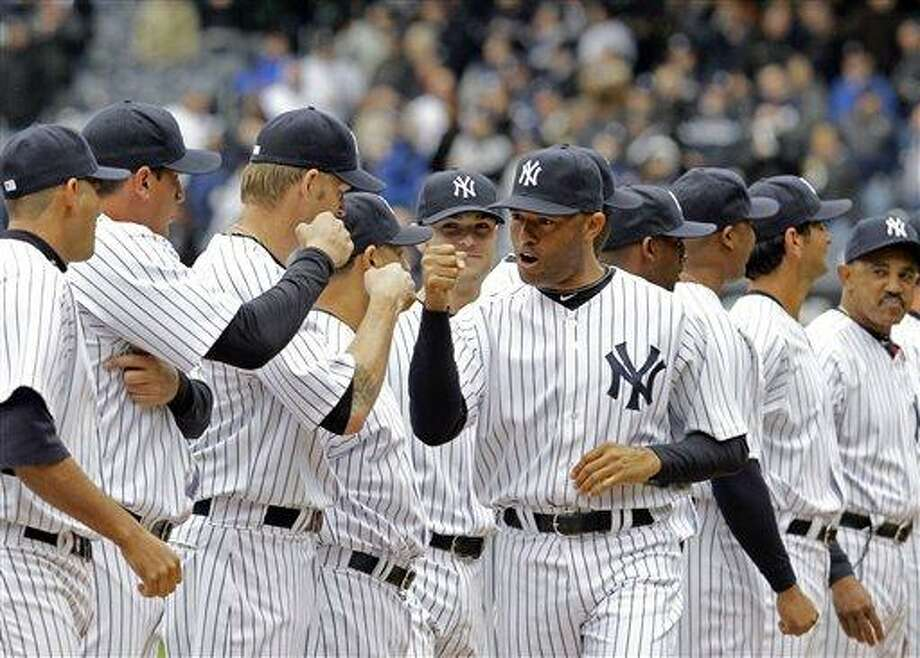 New York Yankees relief pitcher Mariano Rivera, center, greets teammates before their opening day baseball game against the Detroit Tigers at Yankee Stadium on Thursday, March 31, 2011 in New York. (AP Photo/Kathy Willens) Photo: AP / AP