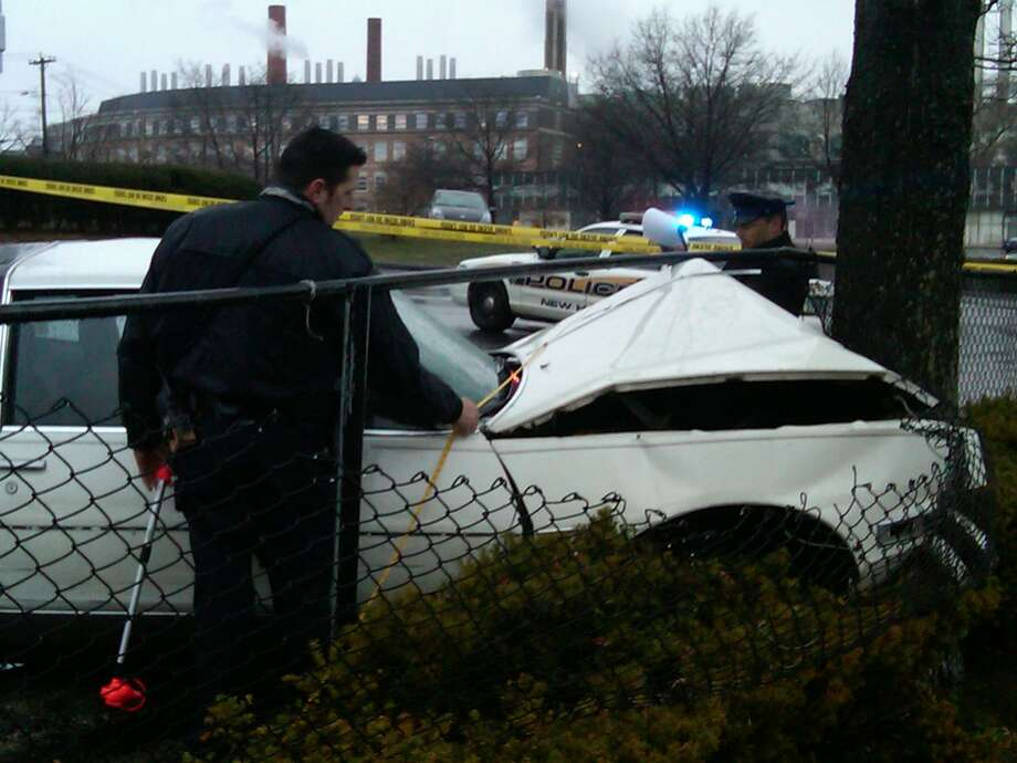 Police at the scene of a crash in New Haven. The driver died and a pedestrian is in 'critical' condition after being struck by the car. Photo by William Kaempffer