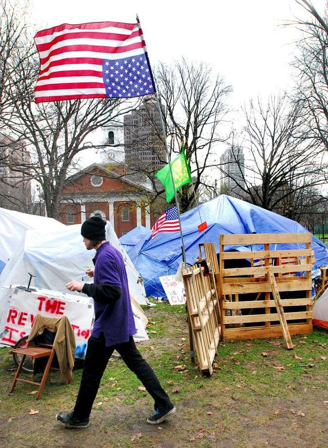 R.J. Creegan of New Haven walks through the Occupy New Haven encampment and by a U.S. flag flown upside-down on the New Haven Green Wednesday. (Arnold Gold/Register)