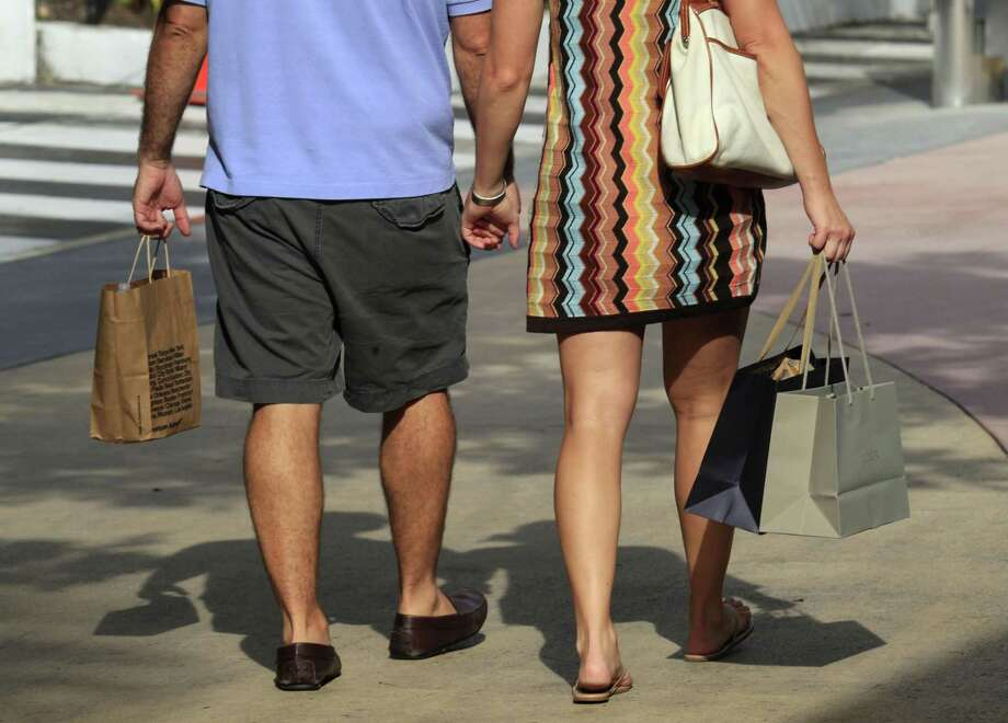 In this Thursday photo, shoppers carry their purchases as they walk along Lincoln Road in Miami Beach, Fla. The Commerce Department said Friday that consumer spending rose 0.2 percent in August after a revised 0.7 percent increase in July. (AP Photo/Wilfredo Lee) Photo: AP / AP
