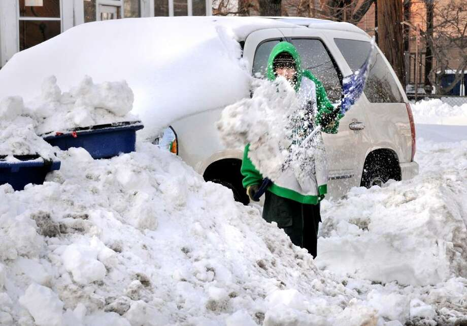 NEW HAVEN-Justin Booker digs his car out on Howard Ave, for the second time.  He had just finished the first job when plows buried the van again.  The recycling bins are also buried.     Melanie Stengel/Register