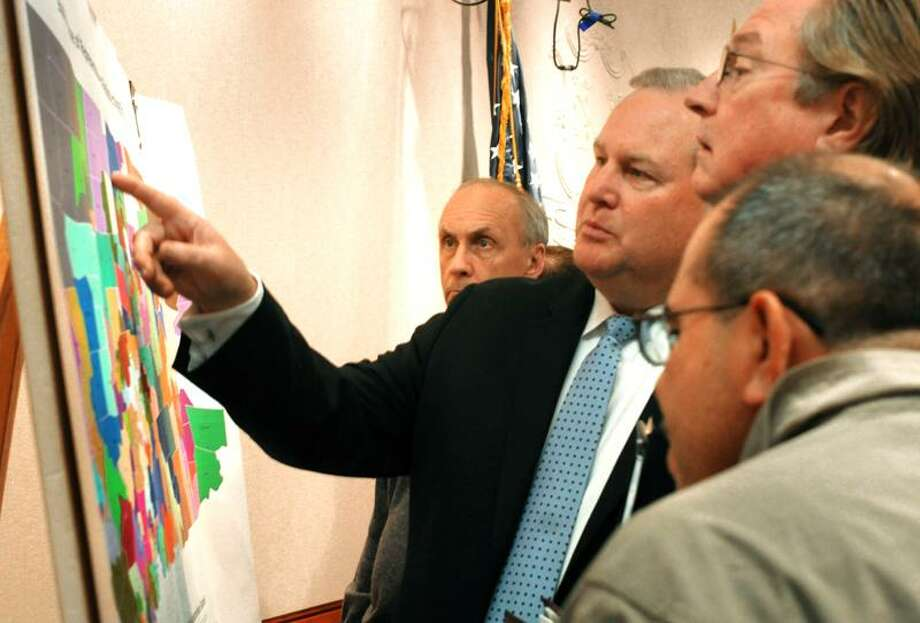 From left, state Reps. William Wadsworth, R-Fairfield, and Rob Heagney, R-Simsbury; Bill Chapman, a lobbyist for the Connecticut Bar Association; and Americo Santiago, chairman of the  Latino redistricting Committee, look over the new map. (Melanie Stengel/Register)