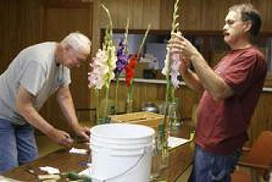 "Dispatch Staff Photo by JOHN HAEGER<a href=""http://twitter.com/oneidaphoto"">twitter.com/oneidaphoto</a>Bob Fietz of Canastota and Dale Rollins of Canastota get Gladiolas ready for the annual show at the 17th annual Ruritan Community Fair in Munnsville on Saturday, July 30, 2011."
