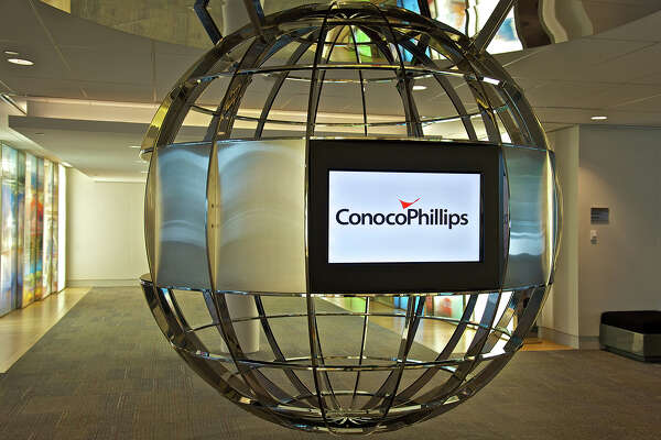 ConocoPhillips reported that it lost $3.4 billion, or $2.78 a share, in the second quarter as it wrote off the value of some assets. The largest independent oil company in the U.S. also said it cut its debt by $3 billion in the quarter.