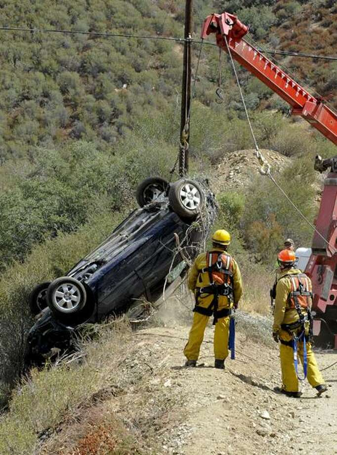 The car of a California man who survived for five days after his car plunged 200 feet off a remote mountain is recovered Friday. Associated Press