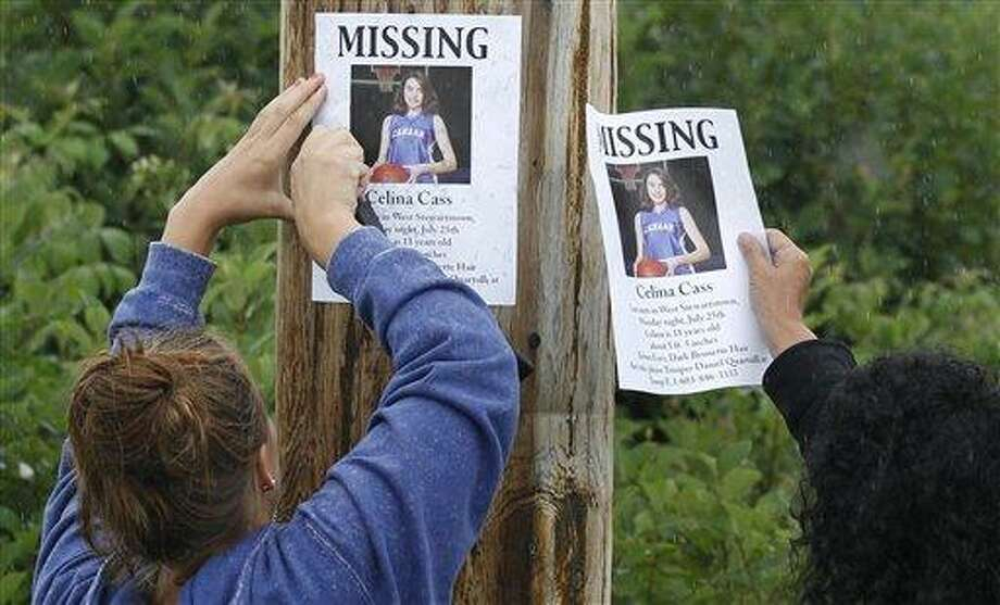 Lori McKearney, of Lancaster, N.H., right, and Kaylin Pettit, of Stewartstown, N.H., post missing posters for 11-year-old Celina Cass in Colebrook, N.H., Wednesday, July 28, 2011.  Cass has been reported missing since she was last seen at her home on Monday evening.  McKearney is Celina Cass's aunt.  (AP Photo/Charles Krupa) Photo: AP / 2011 AP