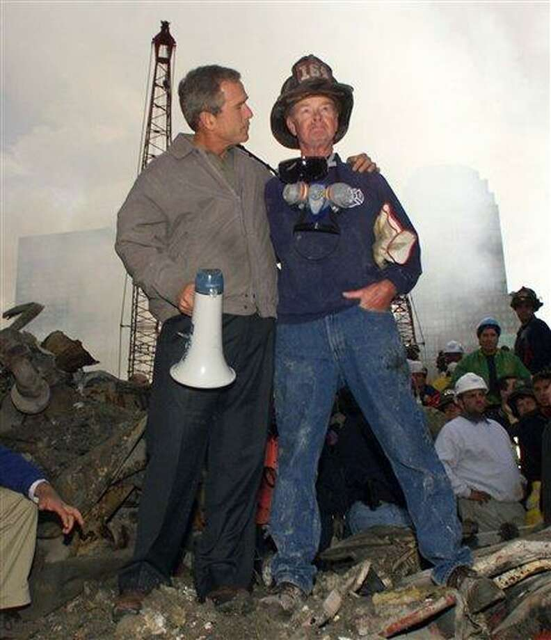 FILE - In this Sept. 14, 2001 file photo, President George W. Bush puts his arm around firefighter Bob Beckwith while standing in front of the World Trade Center in New York during a tour of the devastation. New York City Mayor Michael Bloomberg says former President Bush will be among the dignitaries at a World Trade Center site ceremony to mark the 10th anniversary of the 9/11 attacks. (AP Photo/Doug Mills, File) Photo: AP / AP2001