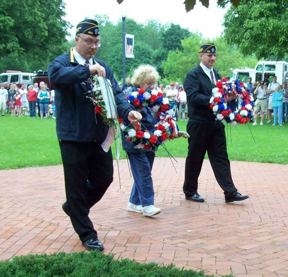 (Photo Special to the Dispatch by MIKE JAQUAYS) Sherrill American Legion outgoing Commander Dave Relyea,left, Auxiliary President Rosemary Sorrentino and incoming Legion Commander Ron Tarry place wreaths at the base of the monument in Memorial Park Monday.