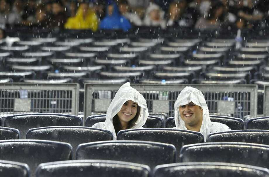 New York Yankees' fans sit in the rain during a rain delay at Yankee Stadium for Game 1 of baseball's American League division series between the Yankees and the Detroit Tigers, Friday, Sept. 30, 2011, at Yankee Stadium in New York. (AP Photo/Kathy Kmonicek) Photo: AP / AP2011