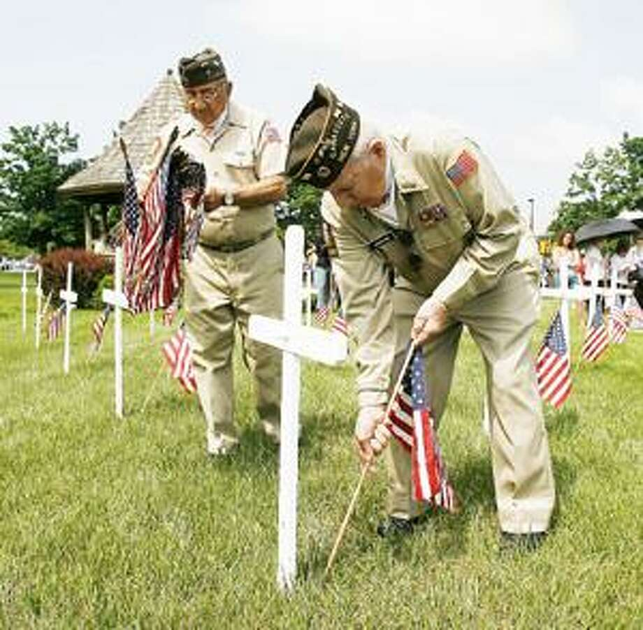 Dispatch Staff Photo by JOHN HAEGER Lou Ezzo and Tom Hughes place flags in front of a cross as the names of the fallen of the Town of Lenox are read during the annual Memorial Day service in Canastota on Monday.