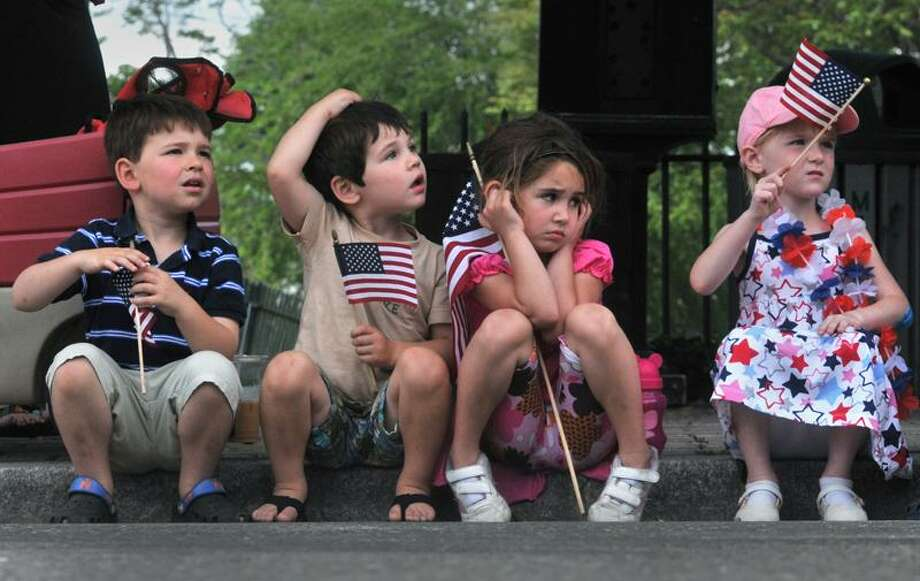 Griffin Fisher, 5, Bradan Fisher, 3, Makenzie Fisher, 5, and Emmy Gagnon, 4, watch the Milford Memorial Day Parade pass by on North Broad Street Sunday. (Brad Horrigan/New Haven Register).