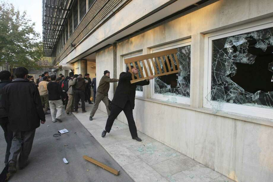 Iranian protesters break the windows of a British Embassy building, in Tehran, Iran, Tuesday, Nov. 29, 2011. Dozens of hard-line Iranian students stormed the British Embassy in Tehran on Tuesday, bringing down the Union Jack flag and throwing documents from windows in scenes reminiscent of the anger against Western powers after the 1979 Islamic Revolution. The mob moved into the diplomatic compound two days after Iran's parliament approved a bill that reduces diplomatic relations with Britain following London's support of recently upgraded Western sanctions on Tehran over its disputed nuclear program. (AP Photo/Vahid Salemi) Photo: ASSOCIATED PRESS / AP2011