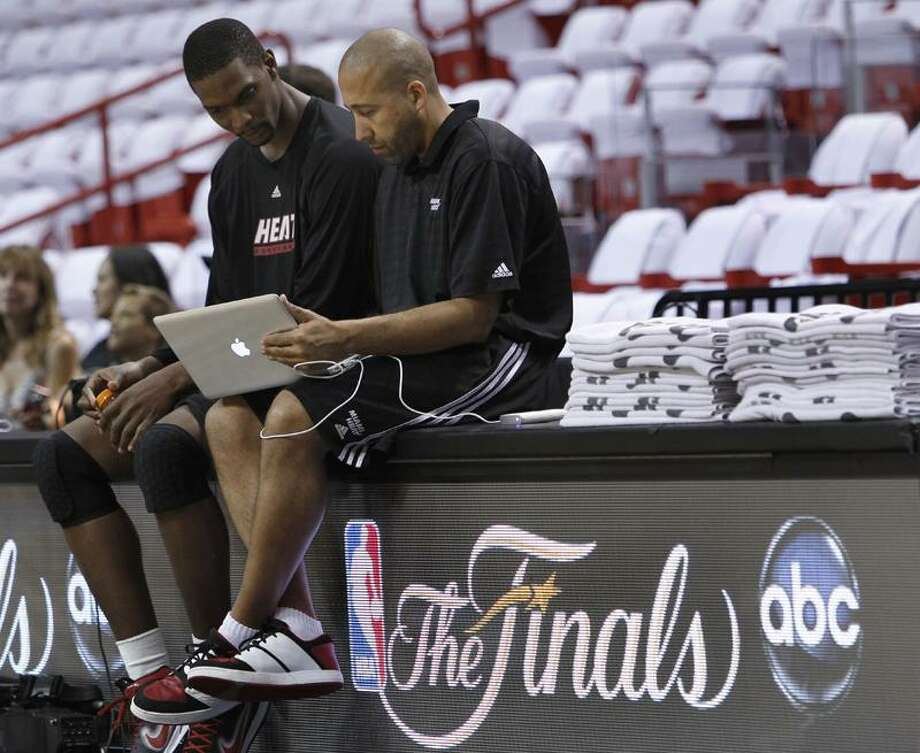 Miami Heat's Chris Bosh, left, talks with assistant coach David Fizdale during practice, Monday, May 30, 2011 in Miami. The Heat will play the Dallas Mavericks in Game 1 of the NBA basketball finals on Tuesday. (AP Photo/Wilfredo Lee) Photo: AP / AP2011