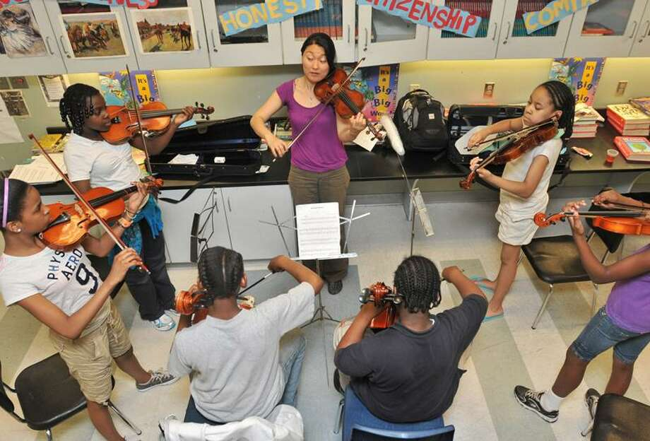 Music Haven resident musician Tina Hadari, center, leads a group of young violinists during a Music Haven practice at Wexler/Grant Community School Friday.  Students clockwise from top left: Shauna Wilson, 10, Denasha Upchurch, 11, Sincere Parsons, 11, Christopher Burney, 10, Donasia Gray, 11, and Jordan Brown, 10. Brad Horrigan/Register